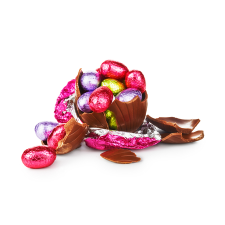 easter egg: Broken chocolate easter egg wrapped in pink foil with colorful candies isolated on white background