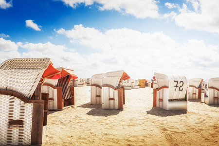 sea beach: White hooded chairs on sand beach. Sunlight and blue cloudy sky. Vacation background. North sea coast, travel destination