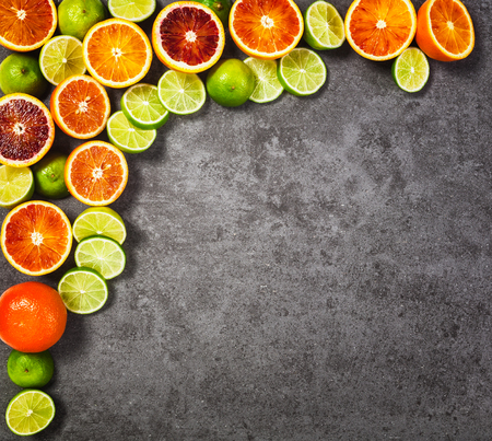 fruit background: Slices of lime and blood orange fruits on grey stone background. Healthy eating and dieting concept. Copy space. Top view