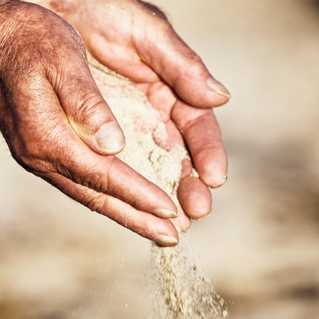 sand grains: Old man hands holding and spilling sand. Shallow DOF Stock Photo