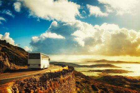 山の道で白の観光バス。ケリー、アイルランドのリング。旅行先