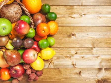fruit basket: Basket of fruits on wooden background. Healthy eating and dieting concept. Winter assortment. Copy space. Top view Stock Photo