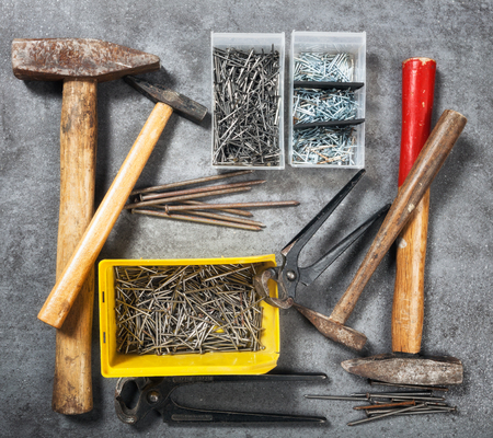 pincers: Tool background. Old vintage hammer, nails and pincers collection on grunge stone workbench. Top view, flat lay Stock Photo