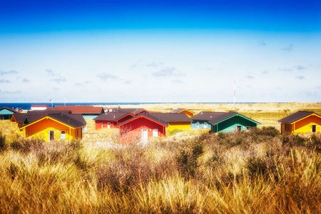 Colorful beach houses in dune grass at the beach of Helgoland, North sea, Germany. Travel destinations. Selective focus Stock Photo