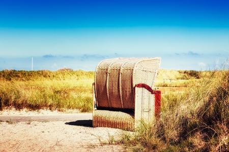 duna: Silla de playa en la hierba de dunas. La luz del sol y el cielo azul. Fondo de las vacaciones. Costa del mar del Norte, destino del viaje. enfoque selectivo