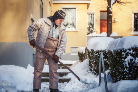 Elderly senior man shovels snow from sidewalk Stock Photo