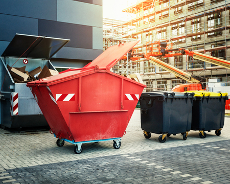 dumpster: Red dumpster, recycle, waste and garbage bins near new office building. Construction site on background