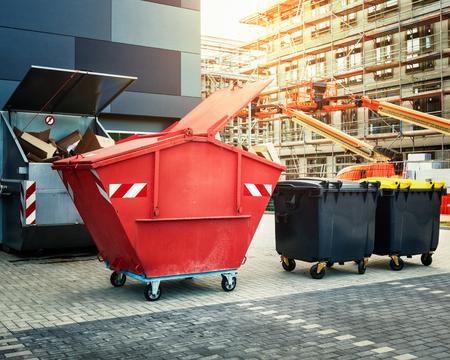Red dumpster, recyclen, afval en vuilnisbakken in de buurt van nieuw kantoorgebouw. Bouwplaats op de achtergrond
