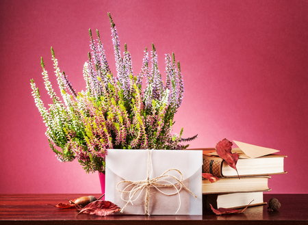 Autumn surprise. Still life with closed white envelope, heather flowers, dry leaves and books