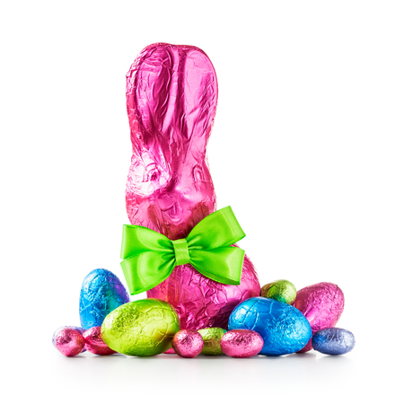 Chocolate easter eggs, rabbit with bow wrapped in pink foil and colorful candies isolated on white background clipping path included Stock Photo