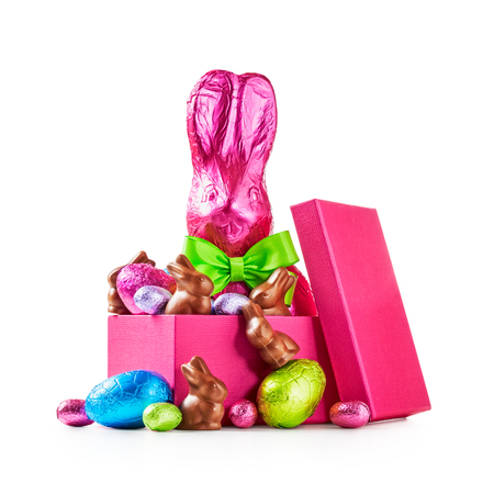 Gift box with chocolate easter eggs, rabbit with bow wrapped in pink foil, bunnies and colorful candies isolated on white background clipping path included