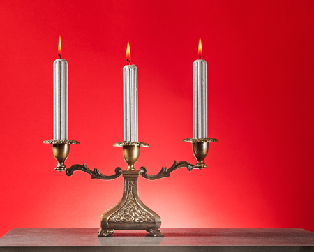 Antique bronze candlestick with three burning silver candles on rot background  Stock Photo