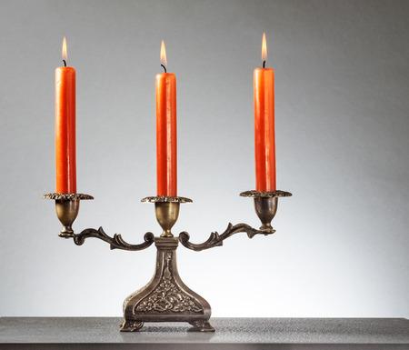 Antique bronze candlestick with three burning orange candles on gray background  Stock Photo