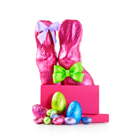 Gift box with chocolate easter eggs, couple of rabbits with bow, wrapped in pink foil and colorful candies isolated on white background clipping path included Stock Photo
