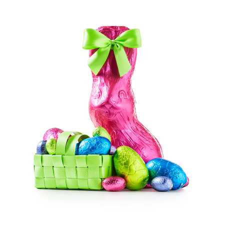 Chocolate easter eggs in basket, rabbit with bow wrapped in pink foil and colorful candies isolated on white background clipping path included Stock Photo
