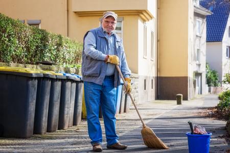 Elderly senior man with broom sweeping sidewalk on sunny day photo