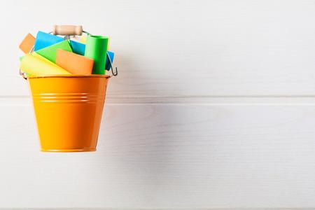 Eimer Liste Konzept. Orange Eimer mit den bunten Papieranmerkungen, die an der weißen hölzernen Wand hängen