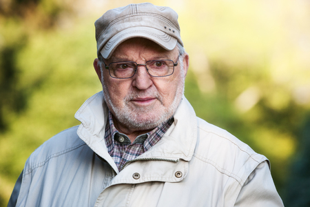 Portrait of senior man outdoors in the park, looking away photo