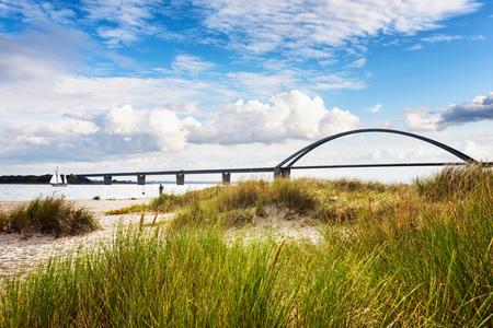 Fehmarn 사운드 브리지입니다. 해변, 모래 언덕 잔디와 흐린 하늘 늦은 여름 풍경. 휴가 배경. 발트 해 연안, 독일, 여행 목적지 스톡 콘텐츠