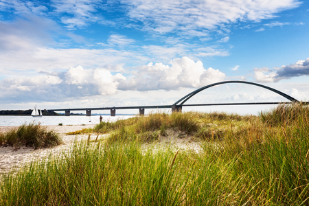 Fehmarn sound bridge. Late summer landscape with beach, dune grass and cloudy sky. Vacation background. Baltic sea coast, Germany, travel destination