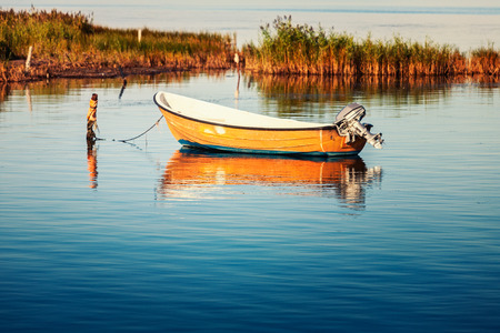 Lonely rowboat with outboard motor on the sea. Autumn landscape, Baltic sea