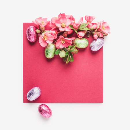Easter greeting card with japanese quince flowers, chocolate eggs and note paper. Holiday composition on white background. Spring arrangement and design element, flat lay 写真素材