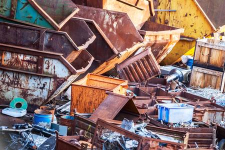 Urban dump junkyard with industrial garbage bins, environmental damage background, selective focus