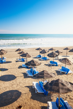 Lounge chairs with sun umbrella on sandy beach, Djerba, Tunisia. Summer background concept, top view 写真素材
