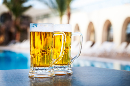 Two beer mugs by swimming pool in tropical resort. Tourism and vacation concept 写真素材