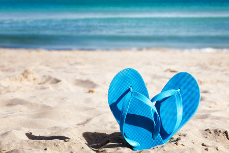 Blue flip flops on sand beach. Summer vacation concept