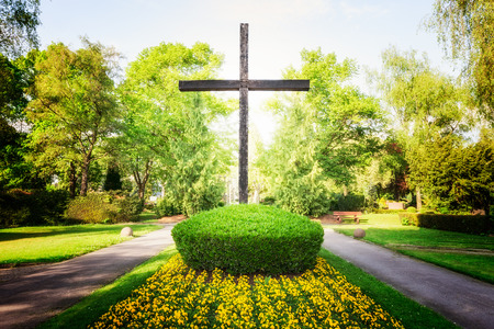 Old wooden large cross at cemetery in springtime. Easter themes