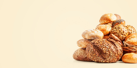 Different fresh bread rolls and buns on bright background. Healthy eating concept