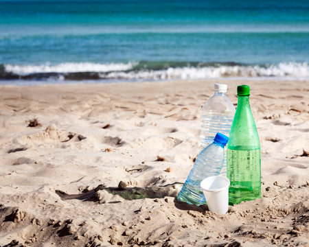 Plastic bottles of water and plastic glass on sand beach abandoned. Tourism and vacation themes. Ocean pollution concept