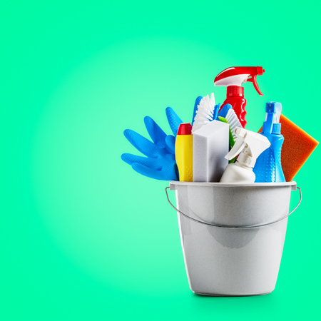 Bucket with cleaning supplies on green background