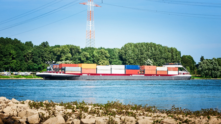 Container ship. Barge shipping containers on the Rhine river, Germany. Summer landscape. Global climate change, drought and low water