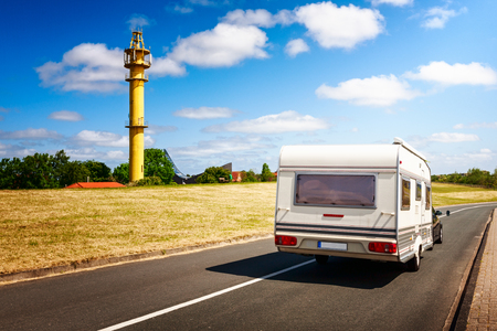 Caravan on the road. North sea landscape with yellow lighthouse on the dike. Family vacation, Germany