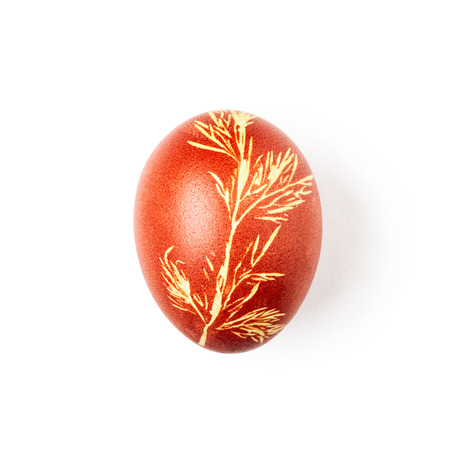 Easter egg handmade with dill leaves imprint natural floral pattern isolated on white background. Holiday symbol and tradition. Single object with clipping path, top view, flat lay Standard-Bild