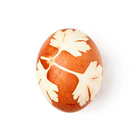 Easter egg handmade with parsley leaves imprint natural floral pattern isolated on white background. Holiday symbol and tradition. Single object with clipping path, top view, flat lay