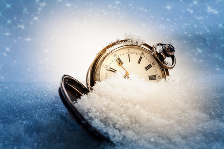 New year clock before midnight. Antique pocket watch in the snow. Holiday concept 免版税图像