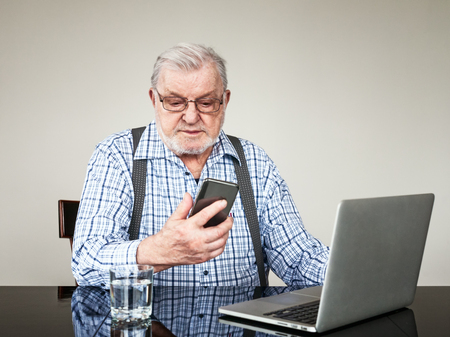 Portrait of active senior man with laptop and smart phone at home. Old man using computer sitting and looking at screen. Elderly pensioner online modern technology concept