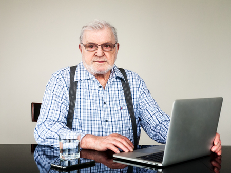 Portrait of active senior man with laptop at home. Old man using computer sitting on chair and looking at camera. Elderly pensioner online, modern technology concept