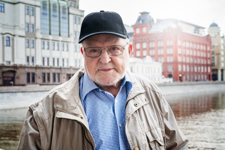 Old man in eyeglasses and cap, traveling in Moscow, standing, posing. Elderly tourist and historic buildings on background. Travel destination