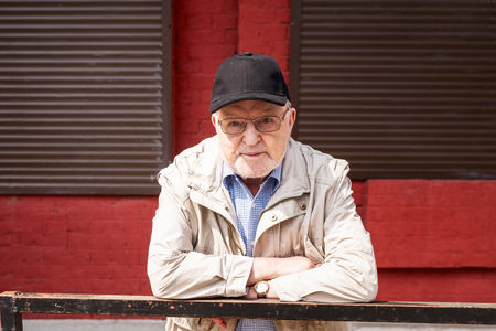 Street portrait of old man in eyeglasses and cap outdoors. Senior posing in front of red wall with windows