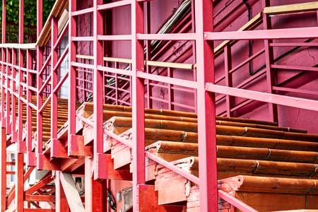 Pink staircase. House under construction and renovation. Perspective view of wooden temporary stairway. Abstract background
