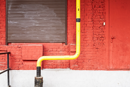 Old brick wall building exterior in coral color with yellow pipe, window and door as background or texture