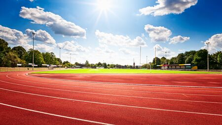Red running track in stadium over blue sky with clouds in summertime Archivio Fotografico - 129495384