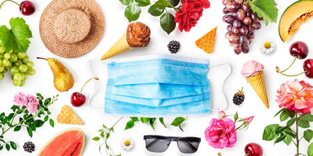 Blue medical mask, straw hat, fruits and flowers isolated on white background. Face mask protection against coronavirus. Coronavirus and pandemic containment concept. Copy space, flat lay