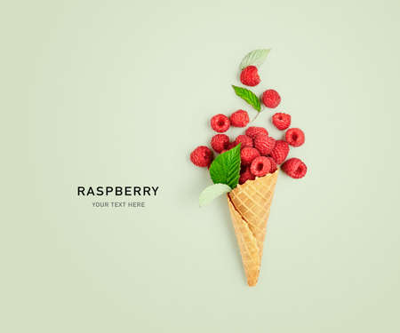 Raspberries in ice cream cone creative layout on green background. Healthy food and dieting concept. Summer raspberry with leaves composition. Top view, flat lay, design card