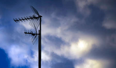 Television antenna over a cloudy blue sky