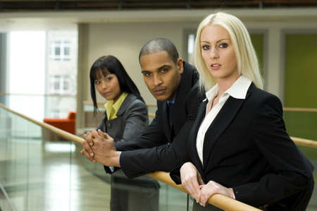 A beautiful business woman at office building with work colleges in the background
